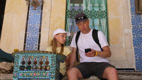Daughter and dad using phone and sitting near house with traditional arabian patterns. Adorable daughter and dad using phone and sitting near house with stock video