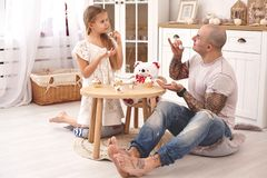 Adorable daughter wearing a white dress whith her loving father. They are drinking tea from a toy dishes in a modern kid stock image