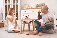Adorable daughter wearing a white dress whith her loving father. They are drinking tea from a toy dishes in a modern kid stock photos