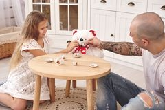 Adorable daughter wearing a white dress whith her loving father. They are drinking tea from a toy dishes in a modern kid royalty free stock photo