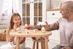 Adorable daughter wearing a white dress whith her loving father. They are drinking tea from a toy dishes in a modern kid royalty free stock photos