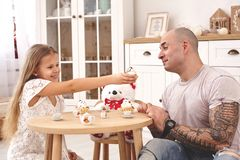 Adorable daughter wearing a white dress whith her loving father. They are drinking tea from a toy dishes in a modern kid stock photography