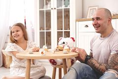 Adorable daughter wearing a white dress whith her loving father. They are drinking tea from a toy dishes in a modern kid stock photo