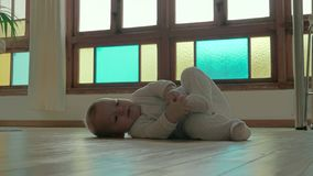 Cute baby playing with foot. Adorable day playing with foot while rolling on floor in stylish room at home stock video
