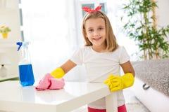 Adorable digno de la muchacha que lleva a cabo el pom y que limpia una tabla en r de vida Imagen de archivo libre de regalías