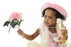 Adorable Diva. Close-up of an adorable two year old diva in pearls, a pink hat, boas and holding a flower while talking on a fancy French phone. On a white stock photos