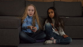Adorable diverse kids watching TV at home. Two multiracial cute long hair girls watching TV and switching channels by remote control while sitting on floor near stock video