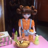 Adorable doll is making orange juice. royalty free stock images