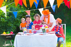 Adorable dutch family having grill party in garden. Happy big Dutch family with kids celebrating a national holiday or sport victory having fun at a grill party Stock Images