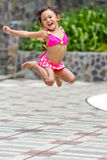 Adorable ethnic child in swimsuit jump high Stock Images