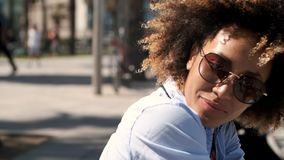Adorable ethnic woman in sunglasses. Portrait of trendy ethnic woman with Afro hairstyle wearing shirt with sunglasses smiling happily at camera in sunlight on stock video footage