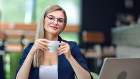 Adorable European business female in glasses holding coffee cup enjoying break at cafe medium shot. Portrait of young stylish businesswoman posing looking at stock video