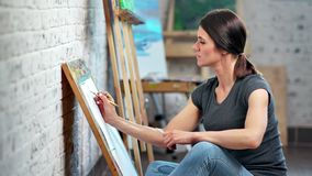 Adorable European female illustrator drawing sketch on canvas using gray pencil medium shot. Focused professional woman artist enjoying working at workshop stock video