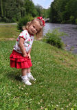 Adorable Explorer. Little girl explores the banks of the Doe River in Tennessee.  She is bent over looking down river Stock Photography