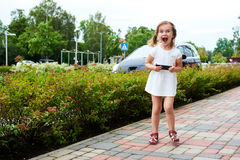 Adorable expressive little girl with a smartphone Stock Image