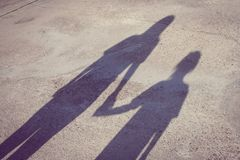 Adorable Family Concept : Shadow on the ground of woman and children standing on concrete floor and holding hand together. royalty free stock photo