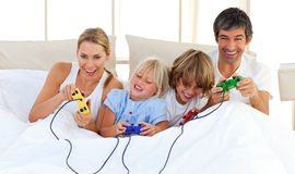 Adorable family playing video game in the bedroom. Adorable family playing video game lying on bed Royalty Free Stock Photography