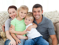 Adorable family sitting on the sofa and smiling Stock Image