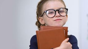 Adorable female pupil in eyeglasses holding books, need of knowledge, genius