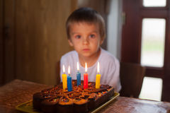 Adorable five year old boy celebrating. His birthday and blowing Stock Image