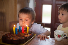 Adorable five year old boy celebrating his birthday and blowing. Candles Stock Photography