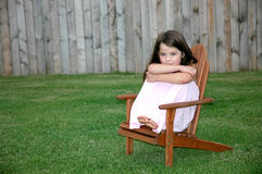 Adorable Five Year Old Girl. Little girl sitting alone in a chair in the backyard Royalty Free Stock Photography