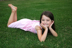 Adorable Five Year Old Girl. Beautiful five year old girl laying in the yard Royalty Free Stock Images