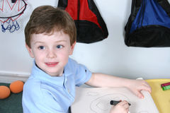Adorable Four Year Old Boy with  Big Blue Eyes Coloring at Presc Stock Photos