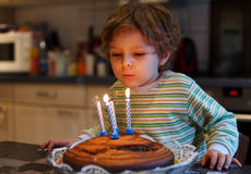 Adorable four year old boy celebrating his birthday and blowing Stock Photo