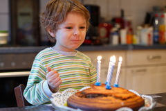 Adorable four year old boy celebrating his birthday and blowing Royalty Free Stock Photo