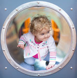 Adorable funny baby girl hiding on a playground Stock Photo