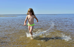 Adorable funny baby girl splashing in the water Stock Images