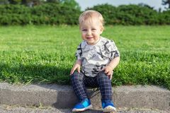 Adorable funny baby toddler boy smiling and sitting on road curb at city park with green grass on background. Cute little child royalty free stock photo