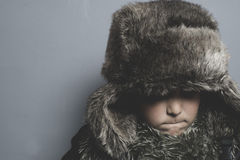 Adorable, Funny child with fur hat and winter coat, cold concept Stock Images