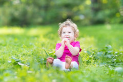 Adorable funny curly baby girl eating candy in sunny park Stock Photo