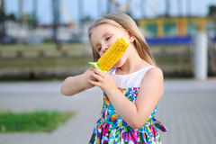 Adorable funny girl eating corn on the cob Stock Photos