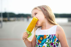 Adorable funny girl eating corn on the cob on sunny summer day Royalty Free Stock Image