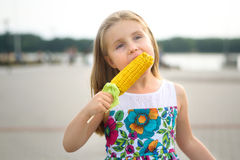 Adorable funny girl eating corn on the cob on sunny summer day Royalty Free Stock Photos