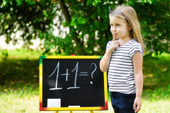 Adorable funny little girl at blackboard practicing counting and math Stock Photos