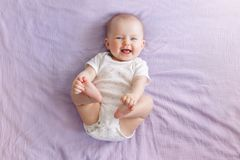 Adorable funny white Caucasian baby with blue eyes lying on back