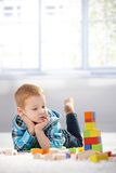 Adorable gingerish little boy with building cubes. Adorable gingerish little boy laying on floor, playing with building cubes royalty free stock photo