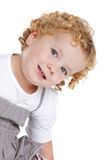 Adorable girl. Cute little girl with blond curls leaning sideways Stock Image