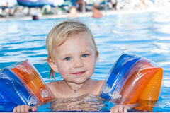 Adorable girl in armbands in swimming pool Royalty Free Stock Photos