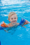 Adorable girl in armbands in swimming pool Royalty Free Stock Image