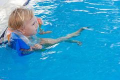 Adorable girl in armbands in swimming pool Stock Images
