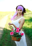 Adorable girl with basket flowers in a field Stock Photography