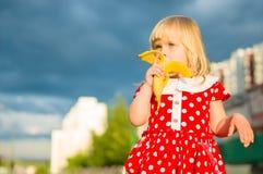 Adorable girl in beautiful dress eat banana Stock Photo