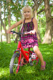 Adorable girl on bicycle in park on grass under trees Stock Photo