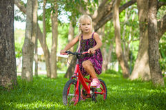 Adorable girl on bicycle in park on grass under trees Stock Photos