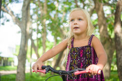 Adorable girl on bicycle in park on grass under trees Royalty Free Stock Photo